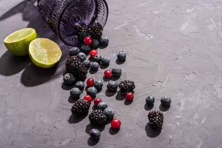Photo pour Gros plan du gobelet en verre avec bleuets épars et tranches de citron vert, smoothie de fruits - image libre de droit