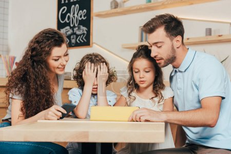 young family using tablet in cafe