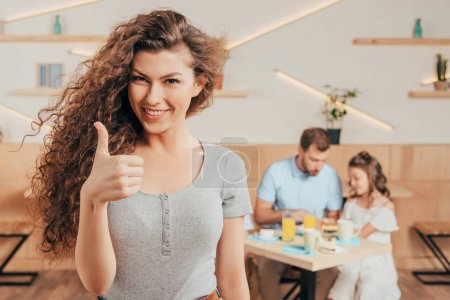 Photo for Young woman showing thumb up in cafe with her family blurred on background - Royalty Free Image