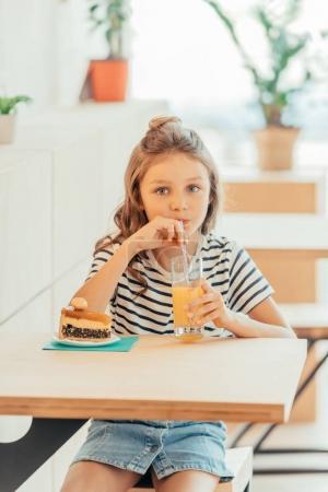 Girl with cake and orange juice