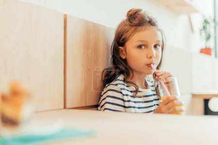 Photo for Cute little girl drinking orange juice while sitting in cafe - Royalty Free Image