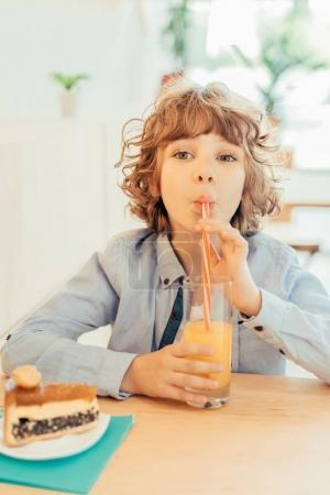 curly boy drinking orange juice