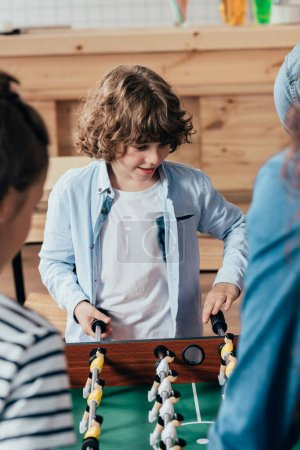 boy playing table football with family