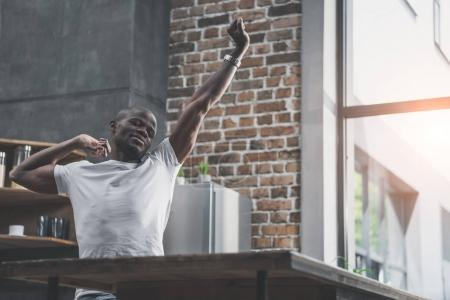 african american man stretching in kitchen