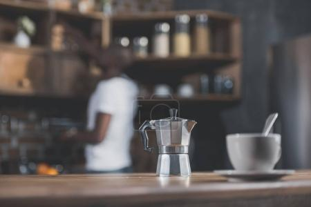 Photo for Close-up view of coffee pot and white cup standing on wooden table in kitchen - Royalty Free Image