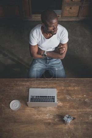 African american man with laptop at table
