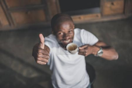 Photo for Handsome african american man showing thumb up and having his morning coffee at home - Royalty Free Image