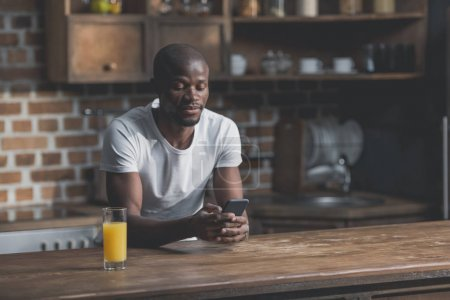 Photo for African american man using phone while sitting in kitchen - Royalty Free Image
