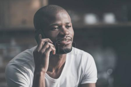 Photo for Close-up portrait of african american man talking on phone - Royalty Free Image