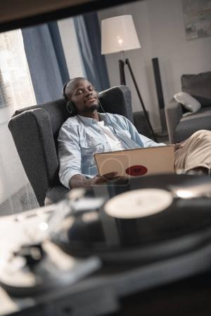 Photo for African american man listening vinyl record at home - Royalty Free Image
