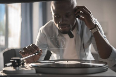 Photo pour Africain américain jouer disque vinyle à la maison - image libre de droit