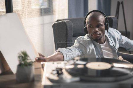 Photo pour Afro-Américain écoute disque vinyle à la maison - image libre de droit