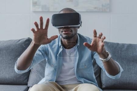 Photo for African american man using virtual reality headset at home - Royalty Free Image
