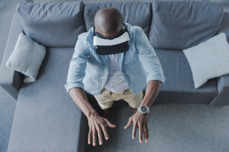 Photo for Overhead view of african american man using virtual reality headset at home - Royalty Free Image