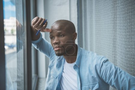 Photo for Portrait of young thoughtful african american man looking at window - Royalty Free Image