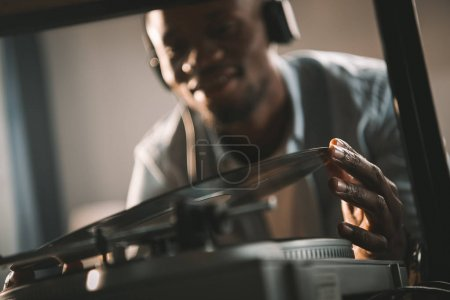 Photo for African american man playing vinyl record at home - Royalty Free Image