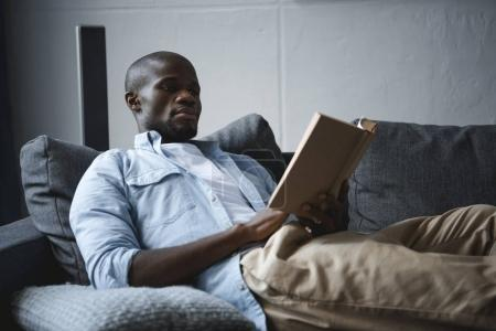 Photo for Handsome african american man reading book at home - Royalty Free Image