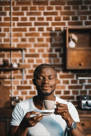 Photo pour Beau Afro-Américain aux yeux fermés prenant son café du matin à la maison - image libre de droit