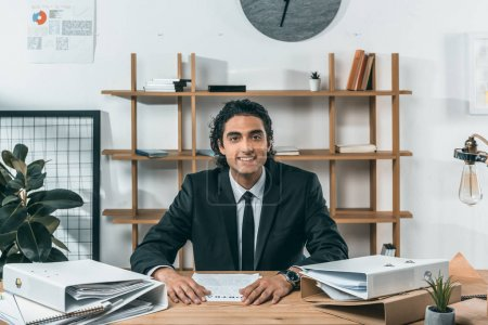 Lächelnder Geschäftsmann am Arbeitsplatz im Büro