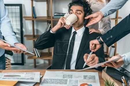 Photo pour Portrait d'un homme d'affaires occupé à boire du café et assis sur le lieu de travail pendant que ses collègues aident au travail au bureau - image libre de droit
