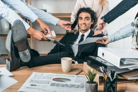 Photo pour Portrait d'un homme d'affaires souriant et occupé assis sur le lieu de travail pendant que ses collègues aident au travail au bureau - image libre de droit