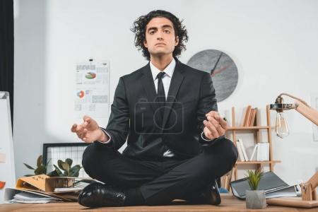 Photo pour Homme d'affaires détendu méditant tout en étant assis sur la table dans la pose de lotus au bureau - image libre de droit