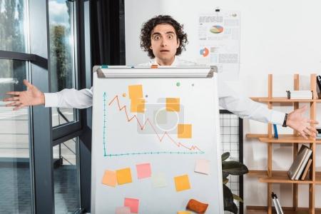 Businessman near white board in office