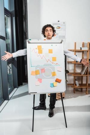 Photo pour Homme d'affaires choqué avec les bras tendus debout près du tableau blanc dans le bureau - image libre de droit