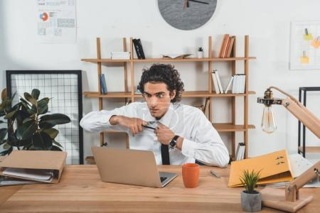 Businessman sitting at workplace with laptop