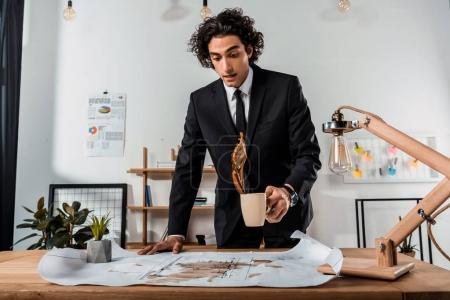 businessman pouring coffee on blueprints