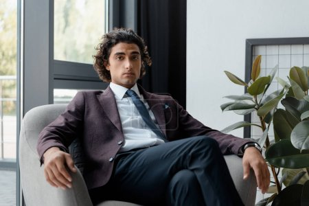 Photo for Portrait of confident businessman in suit sitting in armchair and looking at camera in office - Royalty Free Image