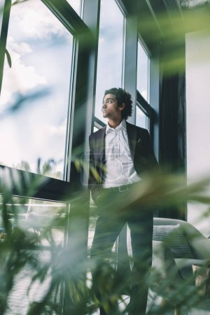Photo for Pensive businessman looking out window while standing in office - Royalty Free Image