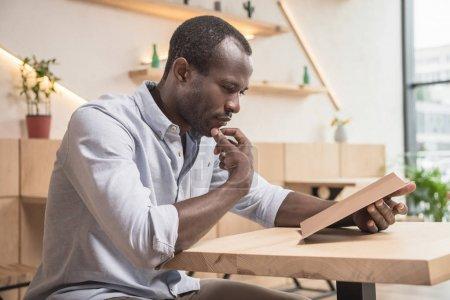 Photo pour Homme afro-américain dans le café en regardant la liste de menu vide - image libre de droit