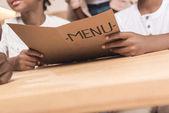 Kids holding menu list