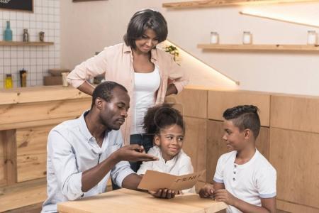 Photo pour Belle famille afro-américaine regardant la liste des menus dans le café - image libre de droit
