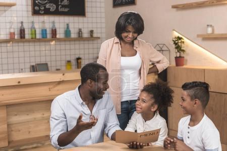 Photo pour Jolie famille afro-américaine regardant la liste des menus dans le café - image libre de droit