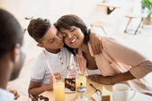 son embracing mother in cafe