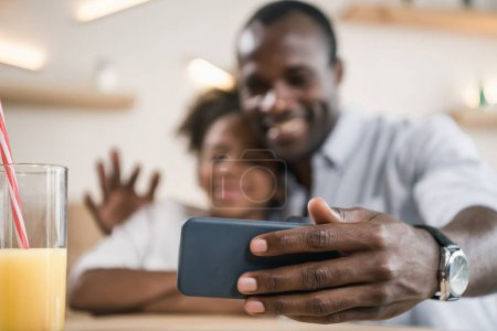 Photo for Close-up shot of african-american father and daughter taking selfie - Royalty Free Image