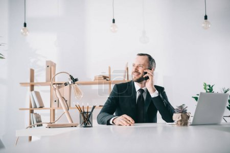 Photo for Smiling young businessman talking by phone - Royalty Free Image