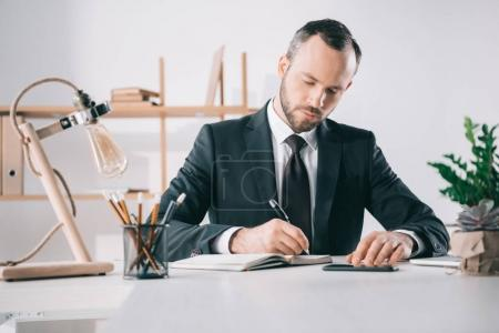 pensive businessman writing in notebook