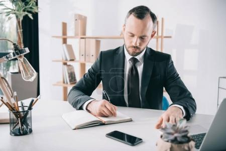 handsome businessman writing in notebook