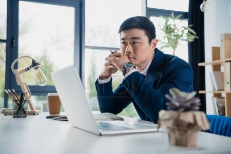 Photo for Focused young asian businessman working with laptop - Royalty Free Image