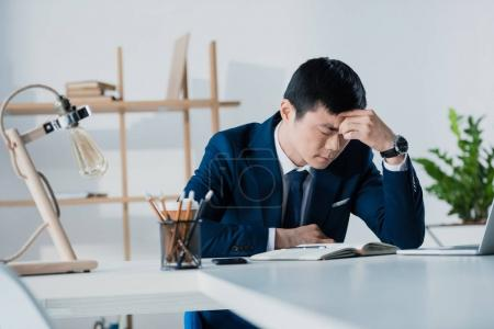 thoughtful overworked asian businessman