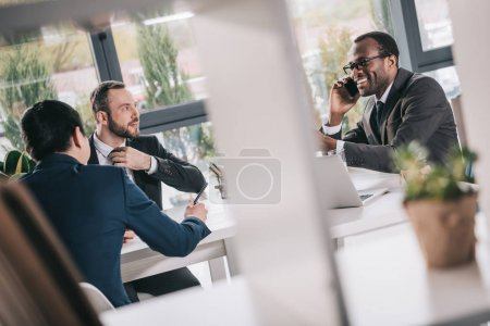 Photo for Team of multiethic businessmen having conversation and smiling - Royalty Free Image