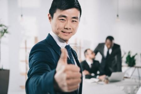 Photo for Asian businessman showing thumb up with blurred colleagues on background - Royalty Free Image