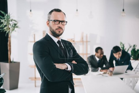 Photo for Attractive young businessman with blurred colleagues on background - Royalty Free Image