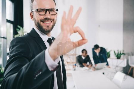 Photo for Handsome young businessman showing okay sign with blurred colleagues on background - Royalty Free Image