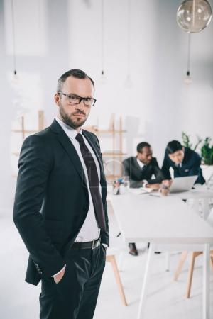 Photo for Handsome young businessman with blurred colleagues on background - Royalty Free Image
