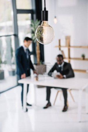Photo pour Lampe vintage avec des collègues de travail assis dans le bureau moderne floue sur fond - image libre de droit
