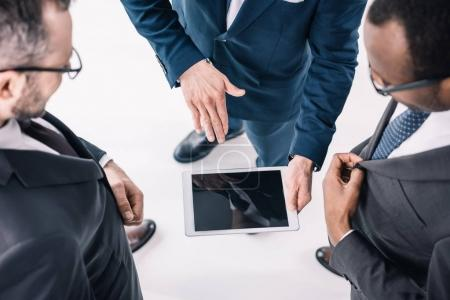 Photo for Top view of group of businessmen looking at tablet - Royalty Free Image